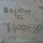 Confidence building quote written in sand at beach: Believe in Yourself
